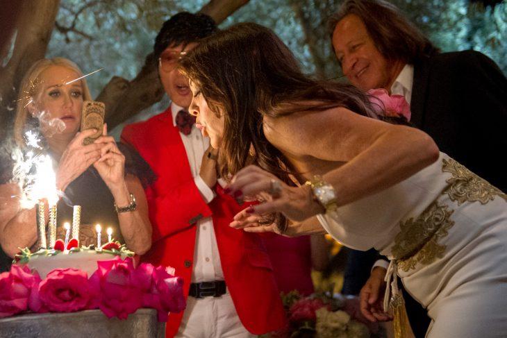 chica soplando velas de pastel