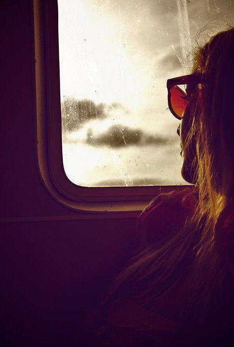 Mujer mirando por la ventanilla de un avión.