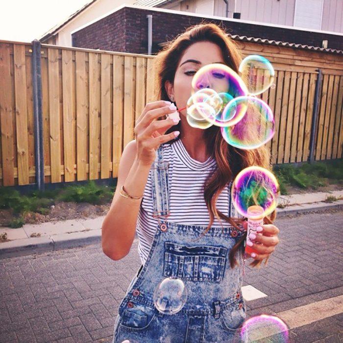 mujer cabello largo juega con burbujas