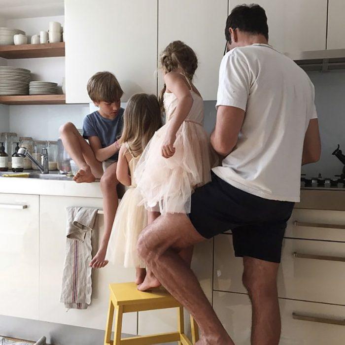 un niño y dos niñas con papa en cocina