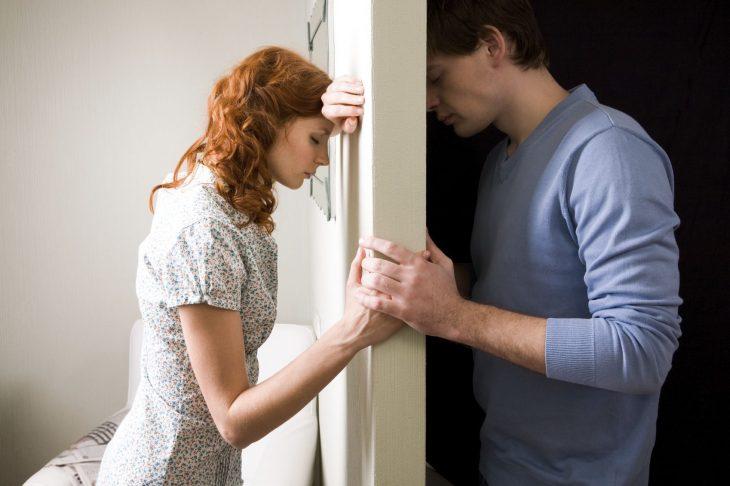 Pareja divididos por un muro, tomándose la mano.