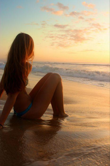 Chica mirando un atardecer en la playa