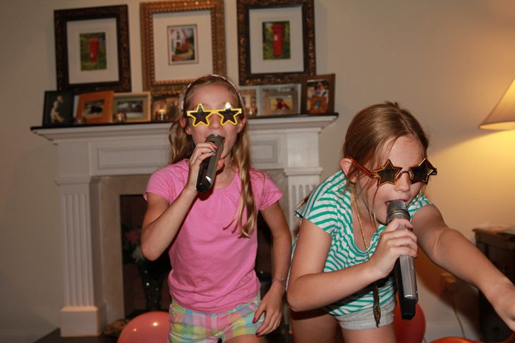dos niñas con microfonos y lentes de estrellas