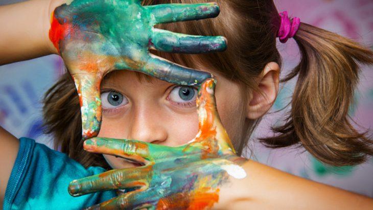 niña con manos pintadas de colores y ojos azules