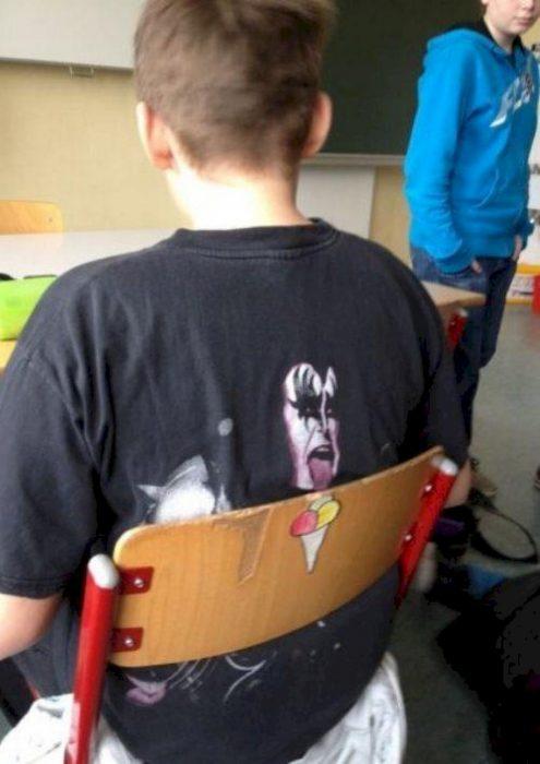 Chico de espaldas con camisa de kiss y hombre sacando la lengua