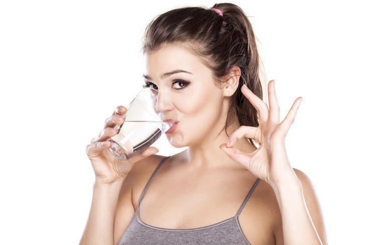 Joven bebiendo un vaso de agua.