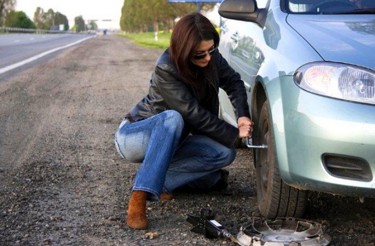 mujer sentada cambiando llanta de coche