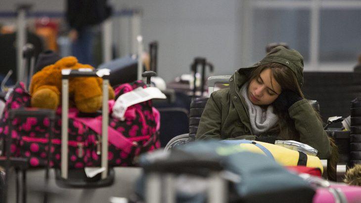 Chica tratando de dormir entre montón de maletas.