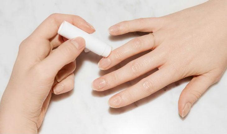 manos de mujer con balsamo para labios en sus dedos