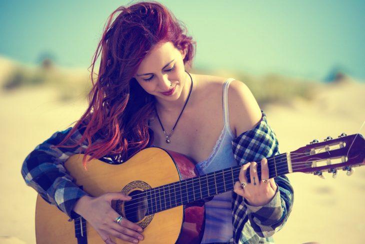 mujer pelirroja con guitarra y camisa de cuadros