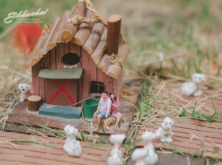 pareja en escenario miniatura con casa y perros