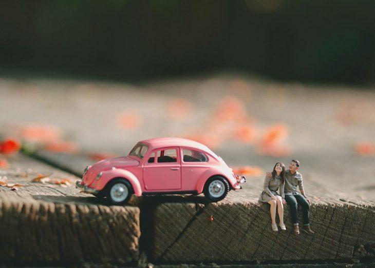 pareja en escenario miniatura coche rosa