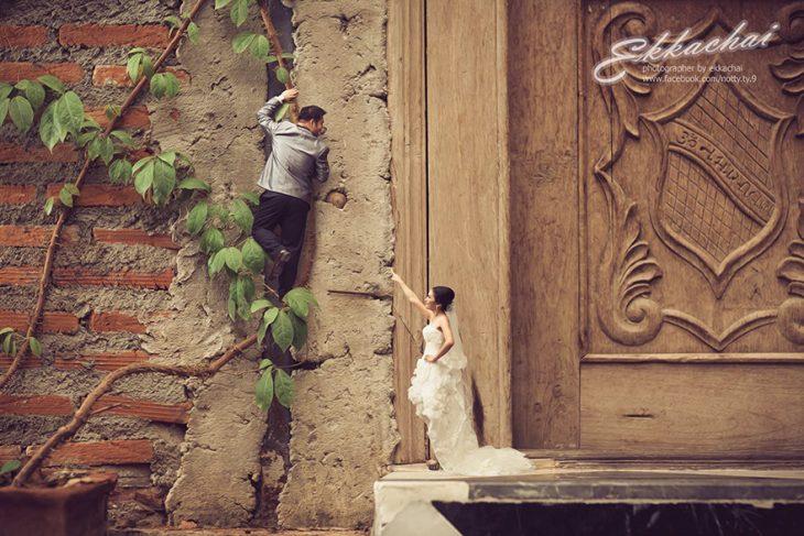 pareja en escenario miniatura hombre subiendo pared y mujer con vestido de novia
