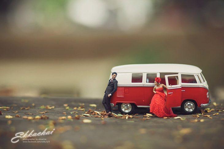 pareja en escenario miniatura saliendo de coche rojo