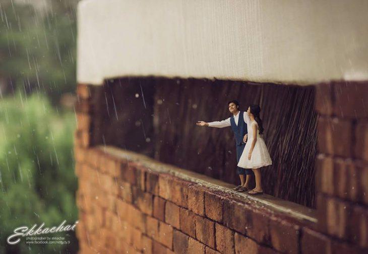 pareja en escenario miniatura bajo techo y la lluvia
