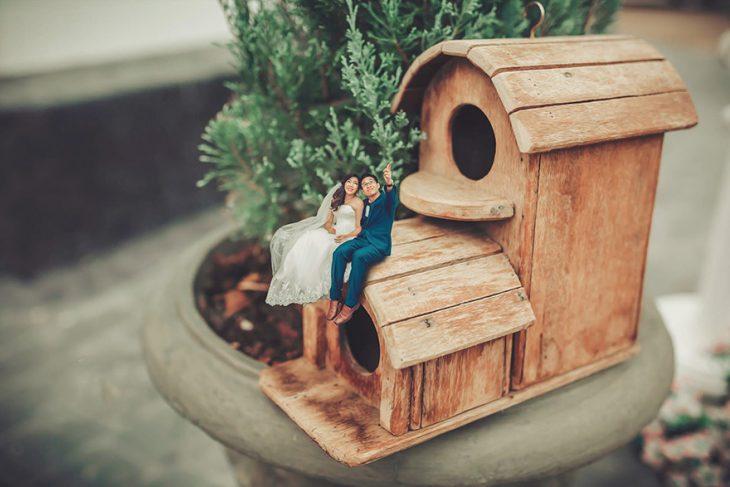 pareja en escenario miniatura sentados en casa de pajaro