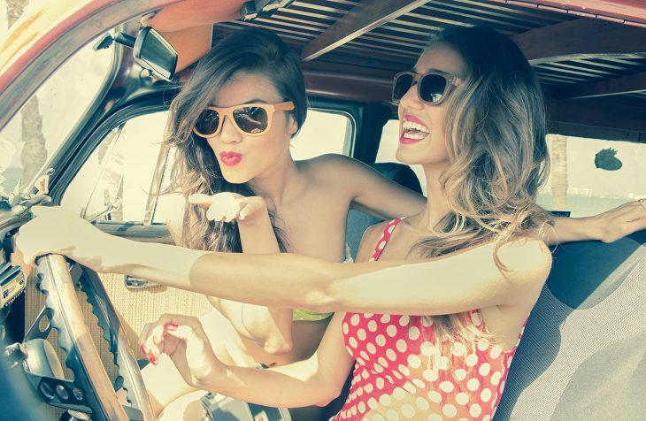 Chicas sonriendo en un coche felices