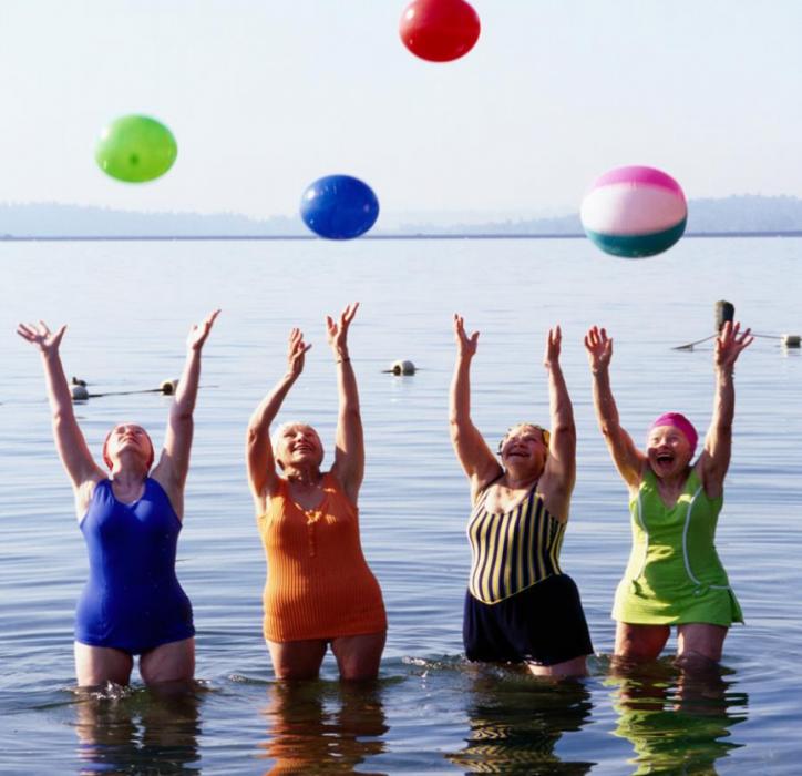 mujeres de 3era edad aventando pelotas en un lago con trajes de baño