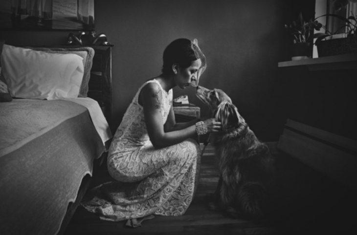 mujer con vestido de novia besando a perro en habitación
