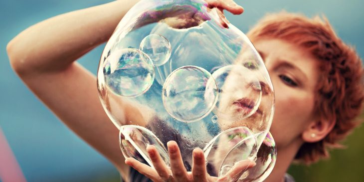 mujer pelirroja jugando con burbujas