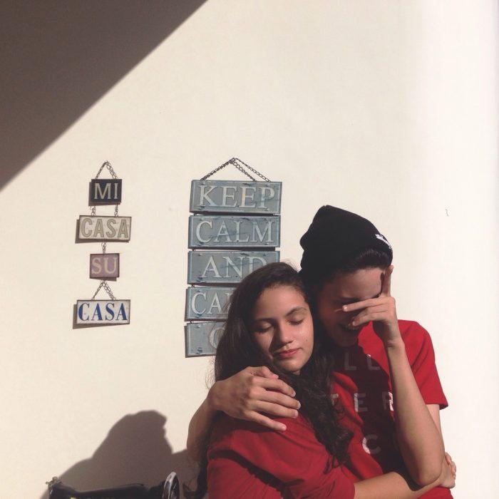 mujeres de abrazandose enfrente de una pared