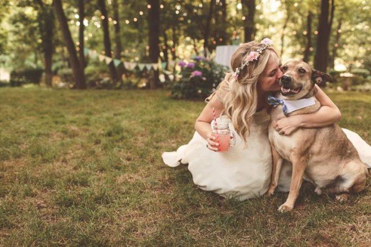 novia con vestido blanco besando y abrazando a perro