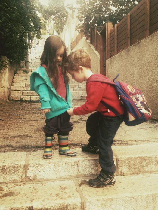 Niño abrochandole el suéter a su hermana.