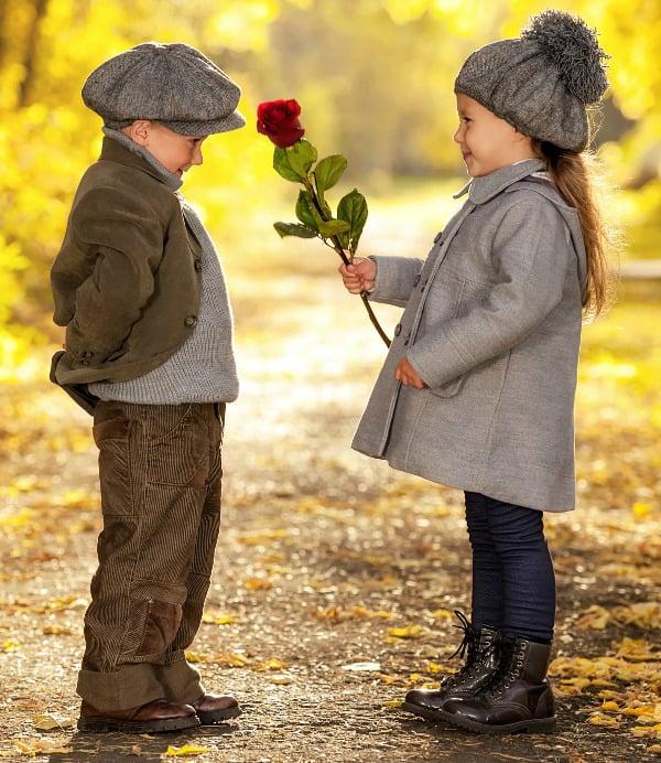 Niña dándole una flor a un niño.