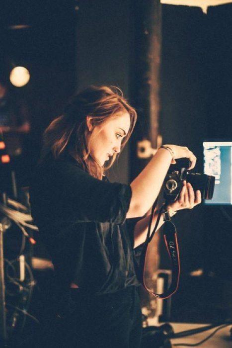 mujer rubia con camara tomando fotos en oscuridad