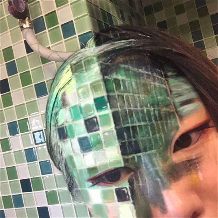 Camuflaje con una pared de azulejos verdes.