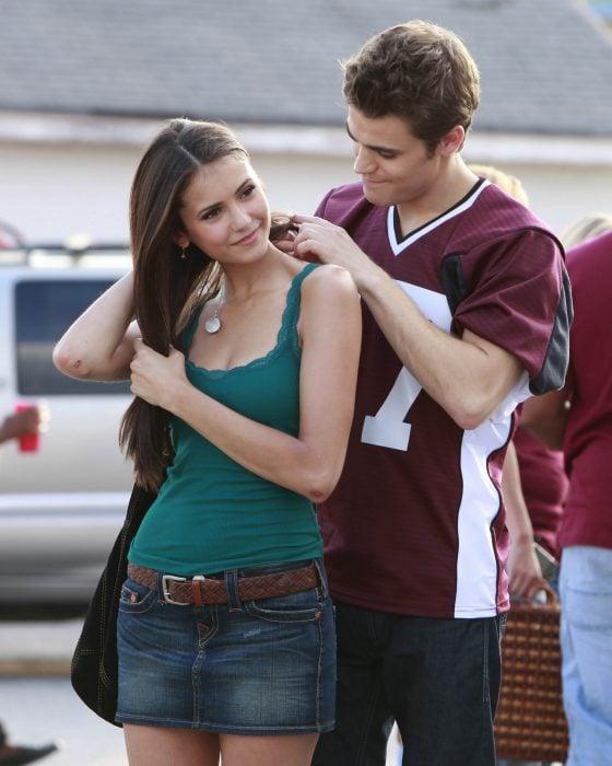 Chico poniéndole un collar a su chica