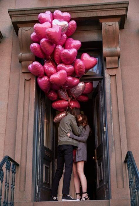 Chico regalandole globos de corazones a su novia