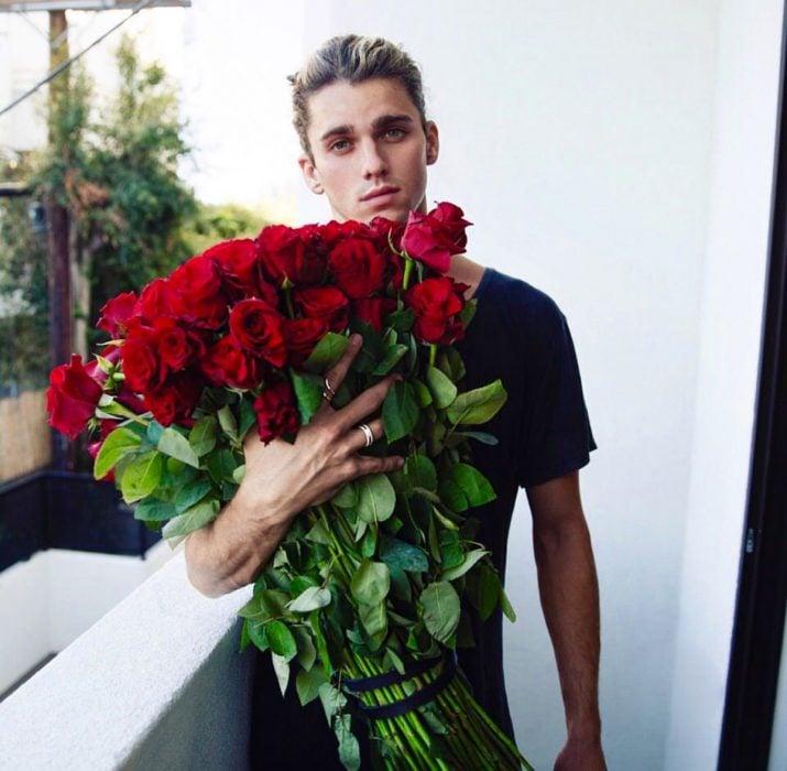 Chico con un ramo inmenso de flores