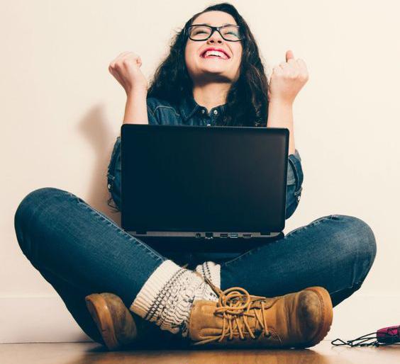 Joven con expresión de felicidad frente a una laptop.