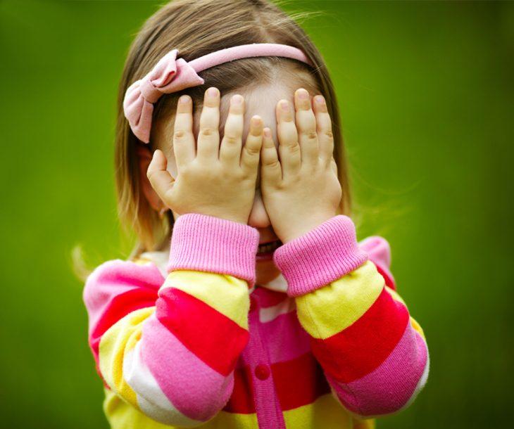 niña con sueter de rayas y manos en su cara