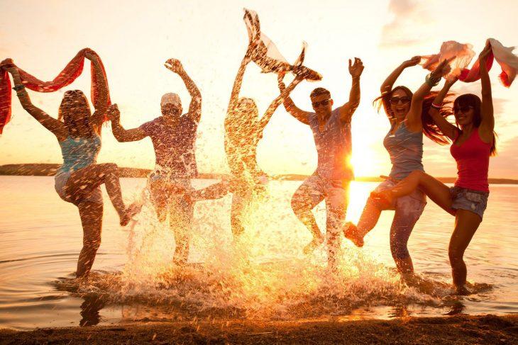Grupo de personas brincando en la playa.