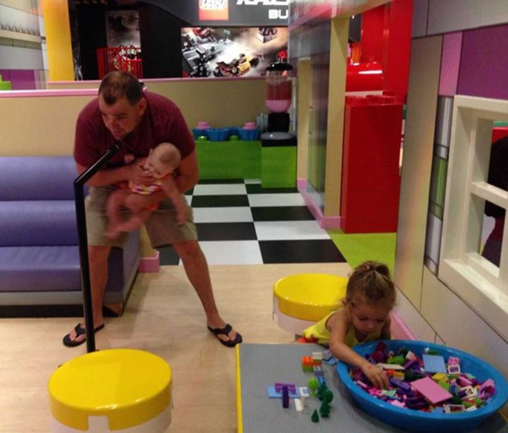 hombre con bebe cantando en microfono y niña con juguetes