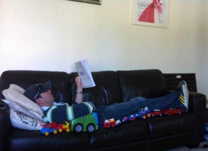 hombre en el sillon leyendo y coches de juguete a un lado