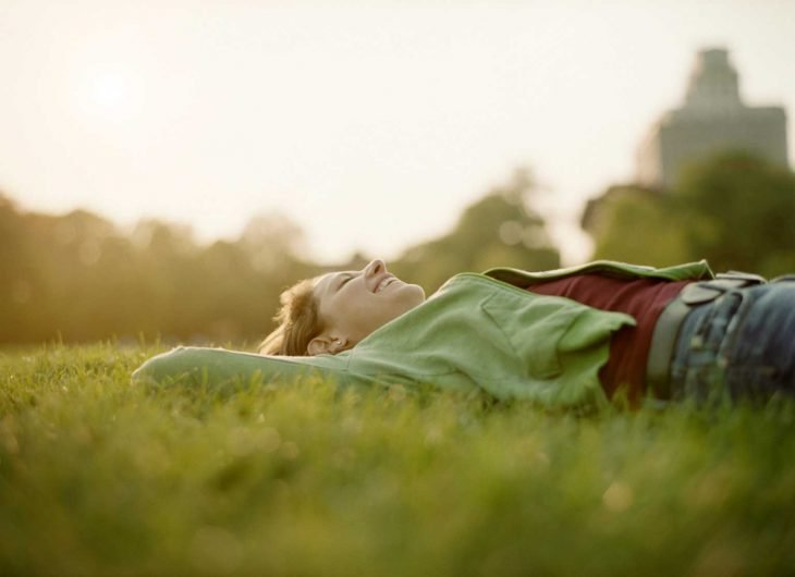 Mujer feliz recostada en el pasto.