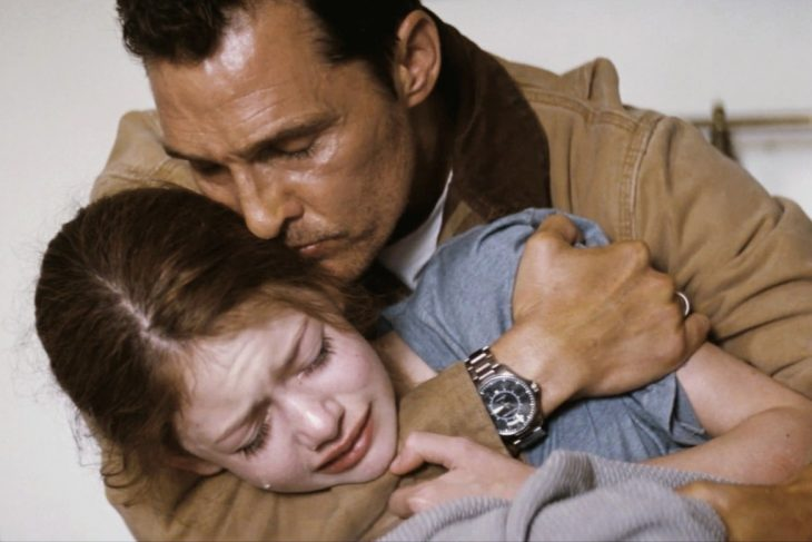 father hugging redhead girl crying
