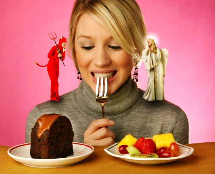 Mujer tentada a comer pastel mientras es aconsejada por el diablo.