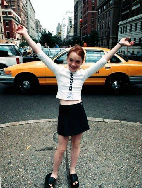 niña con falda y blusa blanca en frente de taxi