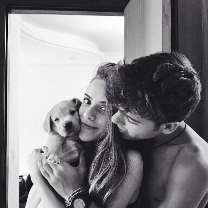 pareja se abraza y traen un cachorro en sus manos