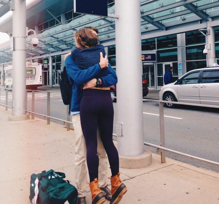 pareja abrazándose afuera de un aeropuerto