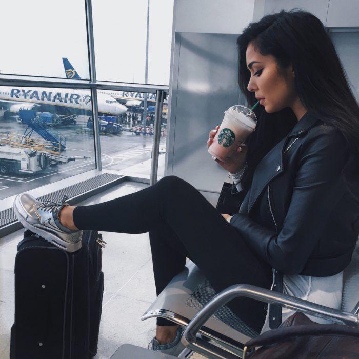 mujer sentada en aeropuerto con maletas y café