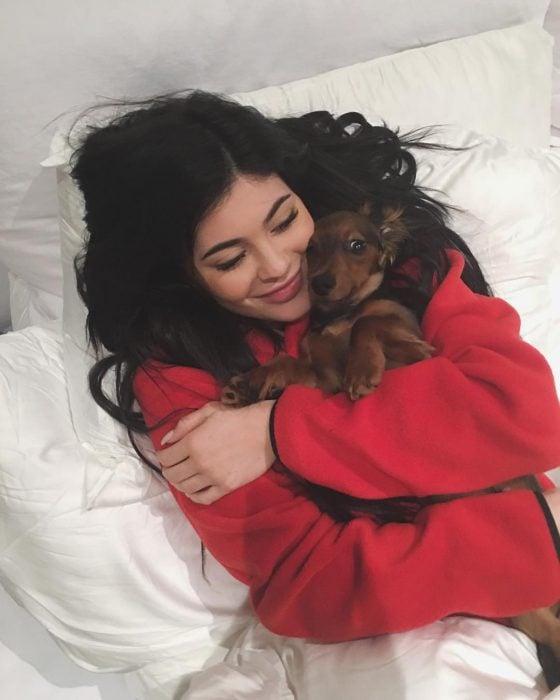 mujer de sueter rojo abrazando a perro en la cama