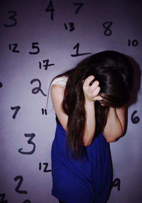 mujer de cabello largo viendo abajo y pared de números