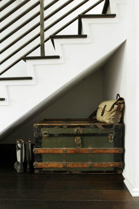 Maleta debajo de unas escaleras.