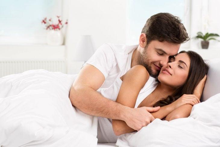 Hombre besando a una mujer en la cama.
