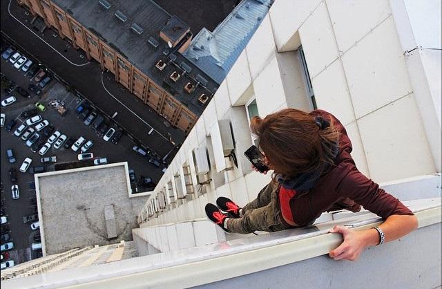 Chica tomando una foto desde la corniza de un edifcio.